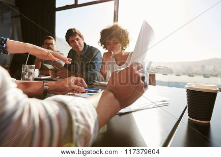 Young Man Explaining Business Plan To Colleagues
