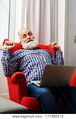 tired senior man with laptop on the chair at home