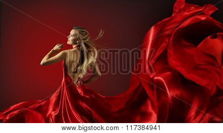 Woman in Red Dress Dancing Fashion Model with Flying Cloth Fabric over red background