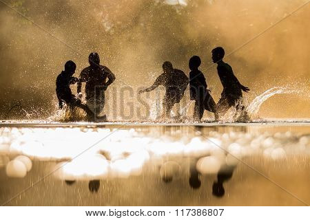 Boys Playfully Splashing Water On Each Other On Holiday.