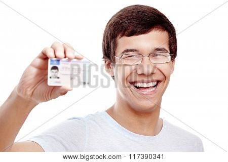 Close up portrait of young hispanic man wearing glasses and blue t-shirt holding out his driving license and smiling isolated on white background - new drivers concept