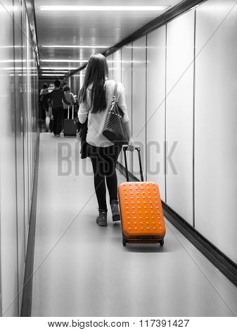woman with orange suitcase on jetway