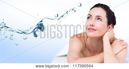 Smiling brunette relaxing on massage table against water bubbling on white surface