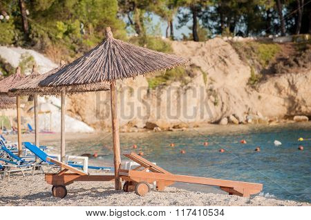 Wooden Sun Beds With Thatched Umbrellas On The Sea Beach