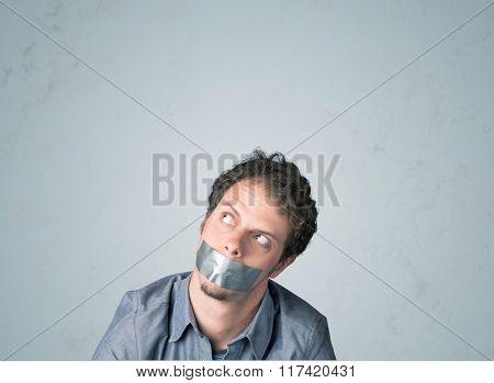 Young man with taped mouth. Isolated on gray background