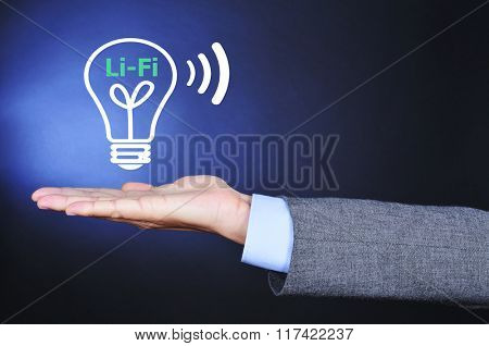 closeup of a man wearing a suit with an illustration of a lightbulb and the text Li-Fi, Light Fidelity, in the palm of his hand