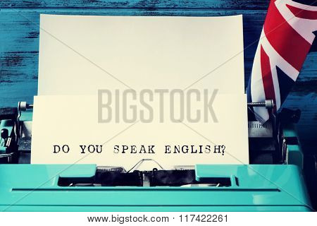 closeup of a paper in an old blue typewriter with the question do you speak english? typewritten in it, and the flag of the United Kingdom