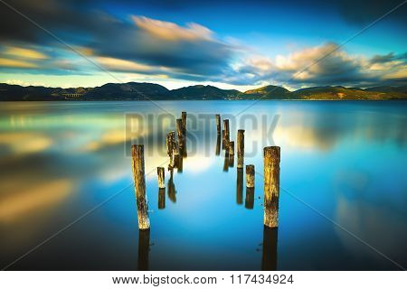 Wooden Pier Or Jetty Remains On A Blue Lake Sunset And Sky Reflection On Water. Versilia Tuscany, It