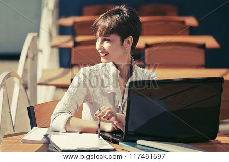 Happy young businesswoman with laptop at sidewalk cafe
