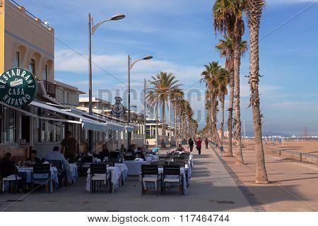 VALENCIA, SPAIN -  NOV 4 2015 : Al fresco diners enjoy their lunch at a seafront restaurant.