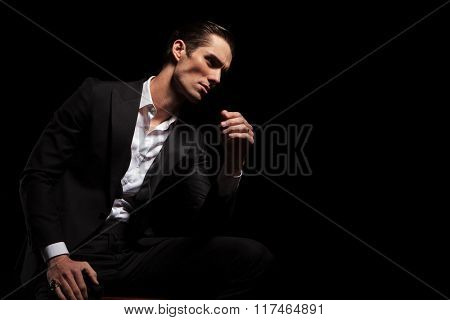 business man in black looking away while seated in dark studio background