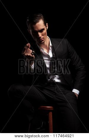 sexy businessman seated in dark studio background with hand in pocket snaps his fingers