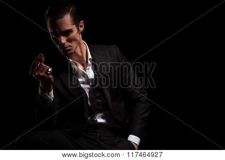 handsome model in tuxedo with hand in pocket snaps his fingers in dark studio background