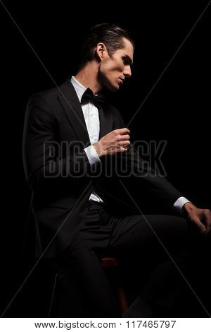 handsome skinny man in black suit with bowtie posing seated in dark studio background while resting his hands and looking away