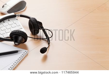 Office desk with headset laying on keyboard. Call center table. View with copy space