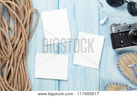 Travel and vacation photo frame and items on wooden table. Top view