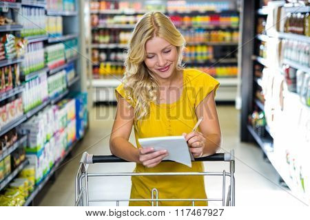 Blonde woman checking list in supermarket