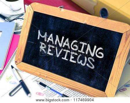 Managing Reviews Handwritten by White Chalk on a Blackboard.
