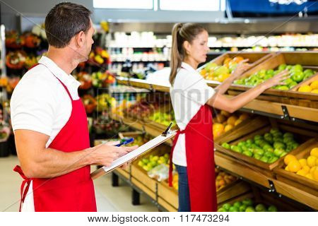 Grocery store staff with clipboard in grocery store poster