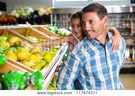 Father giving piggy back to daughter in grocery store