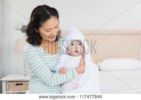 happy mother with baby daughter on the bed