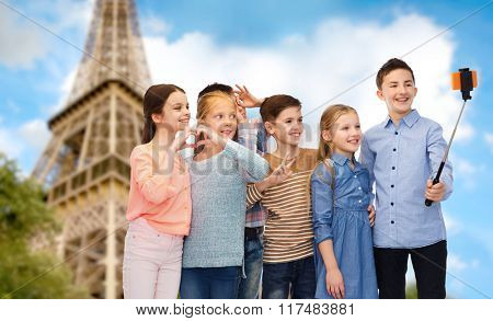childhood, travel, tourism, technology and people concept - happy children talking picture by smartphone on selfie stick over paris eiffel tower background