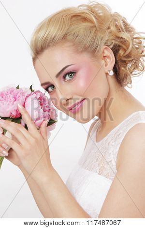 Young beautiful happy bride with stylish prom hairdo and bouquet of peonies