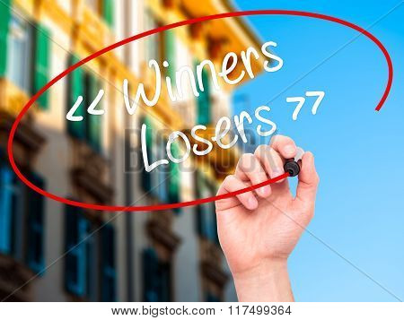 Man Hand Writing Winners - Losers  With Black Marker On Visual Screen