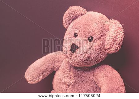 Lonely teddy bear on a dark background looking sad
