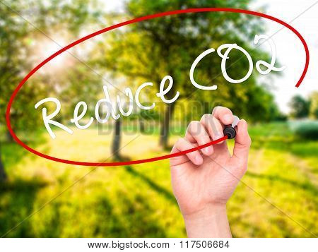 Man Hand Writing Reduce Co2 With Black Marker On Visual Screen.