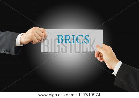 Close-up Of Two Businessman's Hand Holding Paper With BRICS Word On It