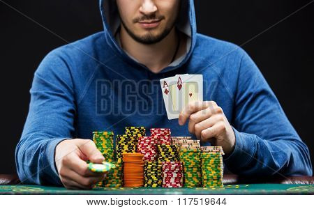 Poker player showing a pair of aces