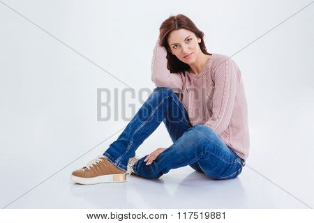 Casual young woman sitting on the floor isolated on a white background