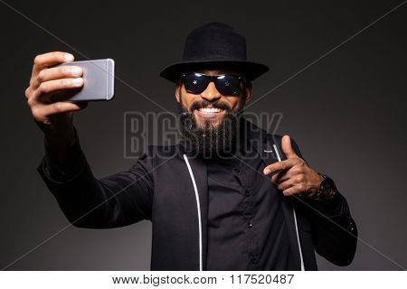 Happy afro american man in fashion cloth making selfie photo on smartphone over black background