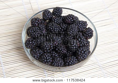 Glass bowl with ripe blackberries