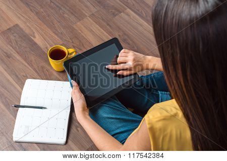Top view photo of young business woman sitting on wooden floor near notebook and cup of coffee. Woman using tablet computer