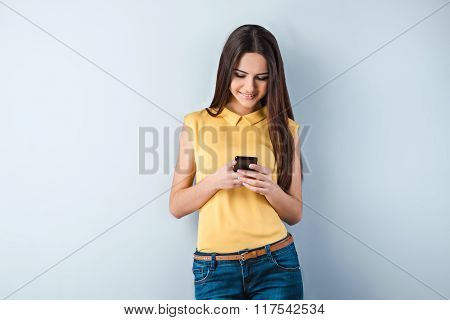 Photo of beautiful young business woman standing near gray background. Woman with yellow shirt using mobile phone