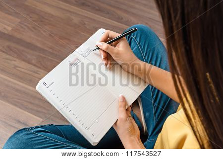 Top view photo of young business woman sitting on wooden floor. Woman holding notebook