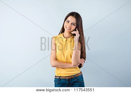Photo of beautiful young business woman standing near gray background. Woman with yellow shirt using mobile phone, looking at camera and smiling