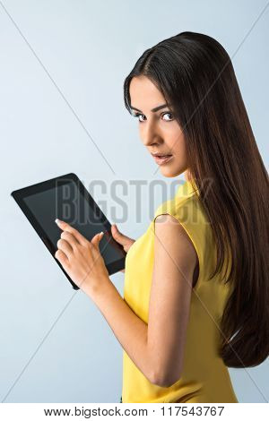 Photo of beautiful young business woman standing near gray background. Woman with yellow shirt using tablet computer and looking at camera