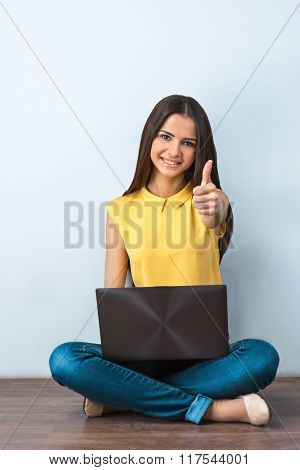 Photo of beautiful young business woman sitting on wooden floor. Smiling woman with yellow shirt using laptop, looking at camera and showing thumb up
