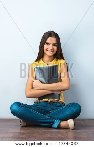 Photo of beautiful young business woman sitting on wooden floor. Smiling woman with yellow shirt holding laptop and looking at camera
