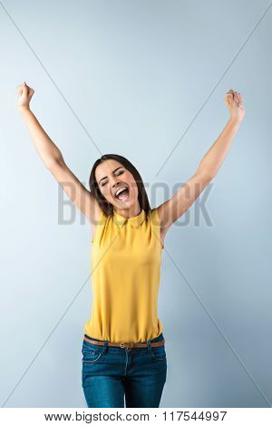 Photo of beautiful young business woman standing near gray background. Happy woman with yellow shirt and arms up cheerfully smiling