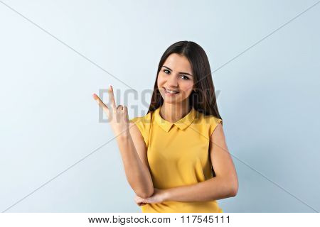 Photo of beautiful young business woman standing near gray background. Smiling woman with yellow shirt looking at camera and showing two fingers