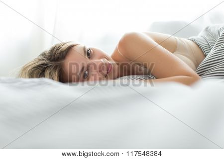 Beautiful young woman sleeping in bed (color toned image; shallow DOF)