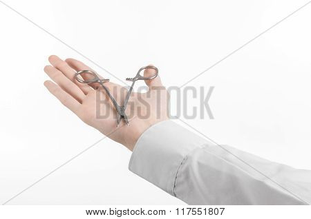 Surgical And Medical Theme: Doctor's Hand In A White Lab Coat Holding A Surgical Clamp Scissors Isol