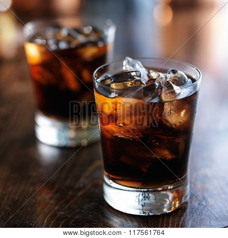 cold fizzy cola soda with ice in glass cup