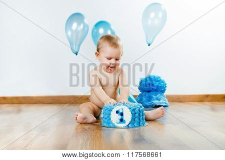 Baby Boy Celebrating Her First Birthday With Gourmet Cake And Balloons.