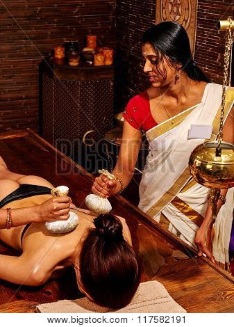 Woman lying facedown having ayurvedic massage with pouch of rice. Passage to India