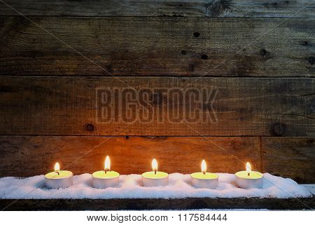 candle light on wooden background with snow